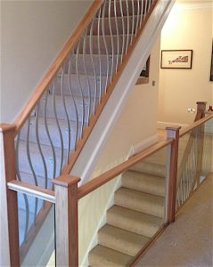 glass gallery balustrade with customer painted forged steel wave spindles in silver up stairway