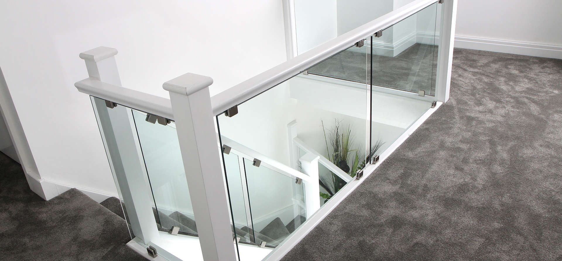 White & Glass staircase and landing area with dark grey carpet