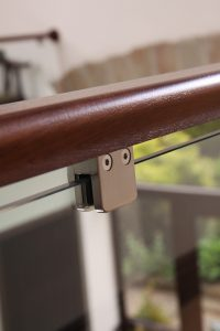 dark wood banister with clamped glass panel