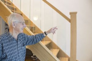 Man pointing to Glass Spindled Staircase